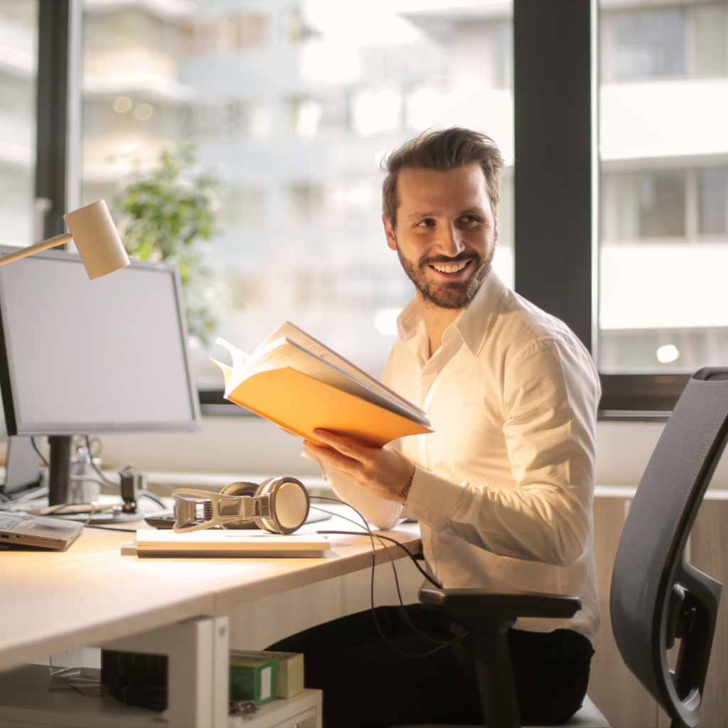 Employee Appreciation | a smiling man in a white shirt holding a yellow book in a working office