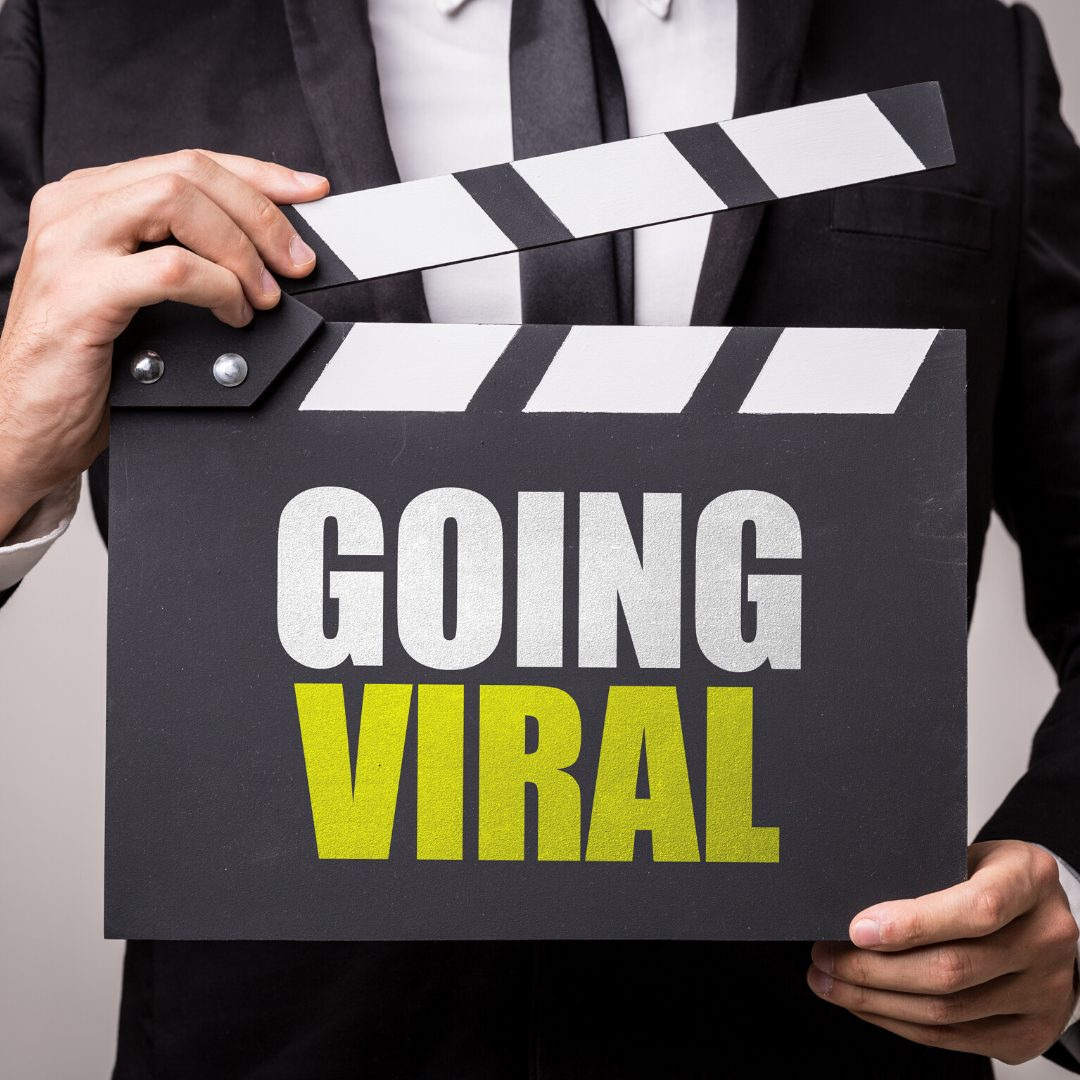 a man wearing a black suit learning how to go viral holding a clapper board