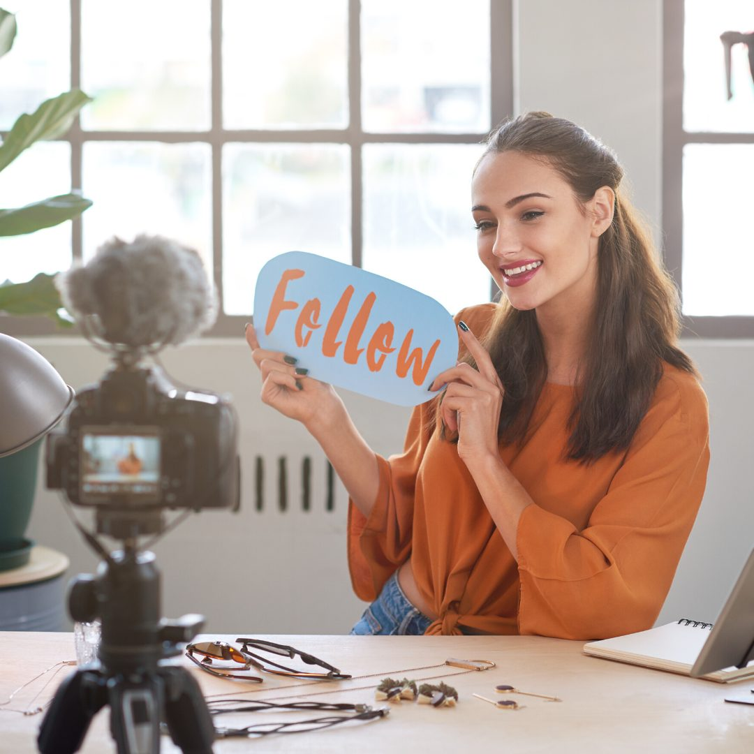 influencer marketing a woman sat in her office smiling at a camera and holding a sign saying follow